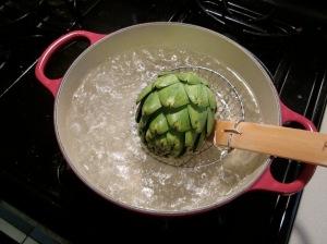 lowering artichoke into pot